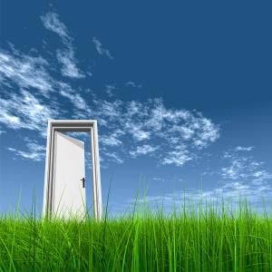 Door opened in grass to the sky