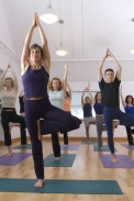Teacher guides student in yoga class